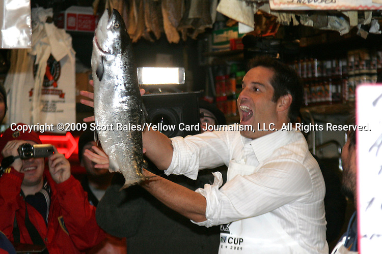 20 November 2009: ESPN broadcaster John Harkes. Major League Soccer players Alan Gordon of the Los Angeles Galaxy and Chris Seitz of Real Salt Lake took part in a fish toss at Pike Place Market in Seattle, WA as part of the Major League Soccer MLS Cup weekend activities.