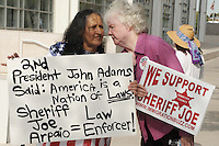 Phoenix, Arizona. July 24, 2012 - Martha Payan (left), and Kathryn Kodor (right), Sheriff Arpaio's supporters, demonstrate outside the Sandra Day O'Connor United States Federal Courthouse in Phoenix, Arizona with signs in favor of the sheriff, as Arpaio testifies in court. Maricopa County Sheriff Joe Arpaio testified in court on July 24, 2012 to respond to accusations his office (MCSO) has been racial profiling Latinos as they enforce local immigration laws in the county. The lawsuit is known as Ortega-Melendres vs. Arpaio. Photo by Eduardo Barraza © 2012