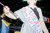 A woman dressed as the Statue of Liberty dances among anti-Trump protesters gather near the Sheraton Portsmouth Harborside Hotel in Portsmouth, New Hampshire, USA. At the hotel later that evening, Republican presidential candidate and real estate mogul Donald Trump received an endorsement from the New England Police Benevolent Association executive council. Many protesters expressed disagreement with Trump's recent statements that he would ban all Muslims from entering the country. Trump brought up the recent shooting in San Berdardino, Calif., at the meeting. A small group of perhaps 20 Trump supporters stood outside the hotel. One of the protest organizers estimated that there were around 230 protesters gathered.