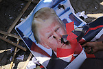 Palestinian women burn posters depicting U.S. President Donald Trump during a protest against US President Donald Trump's decision to recognise Jerusalem as the capital of Israel, in Gaza City on December 17, 2017. Photo by Ashraf Amra