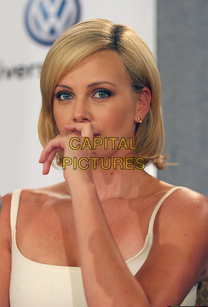 "CHARLIZE THERON.""North Country"" Press conference held at Sutton Place,.Toronto Film Festival,.Toronto, 12th September 2005.portrait headshot white strappy top hand face nose.Ref: FARR.www.capitalpictures.com.sales@capitalpictures.com.© Capital Pictures."
