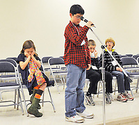 Bradley Elementary 3rd grader Kyra Holland (left) and Cedar Lee 6th grader Matthew Schwindt (3rd from left) show their nervousness, fatigue, or sleepiness as P. B. Smith Elementary 5th grader Gehrig Faircloth struggles at a point in the middle of spelling a word late in the night when only four students remain during the Fauquier County Spelling Bee 2011 at Auburn Middle School on Thursday night.