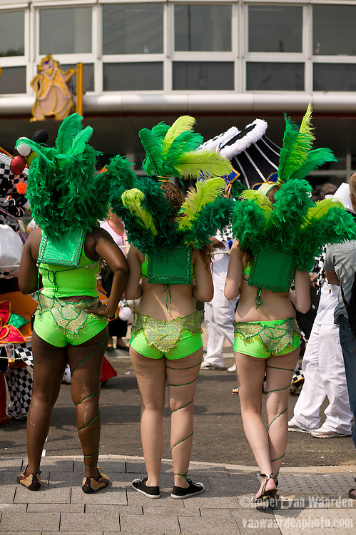 The backs of three participants waiting for their turn to join the parade for the ZomerCarnaval (Summer Carnival) in Rotterdam, the Netherlands. The street parade is the colorful high point of the Rotterdam carnival. It is a tropical themed parade with over 2000 participants and travels 6km through the center of Rotterdam.