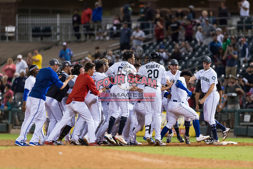 AFL West catcher Meibrys Viloria (9), of the Surprise Saguaros and Kansas City Royals organization, tries to touch first base while being mobbed by his teammates after hitting a game-winning walk-off single in the bottom of the ninth inning of the Arizona Fall League Fall Stars game at Surprise Stadium on November 3, 2018 in Surprise, Arizona. The AFL West defeated the AFL East 7-6 . (Zachary Lucy/Four Seam Images)