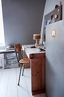 A simple work room is furnished with a desk made of scrap wood and a chair found in a flea market