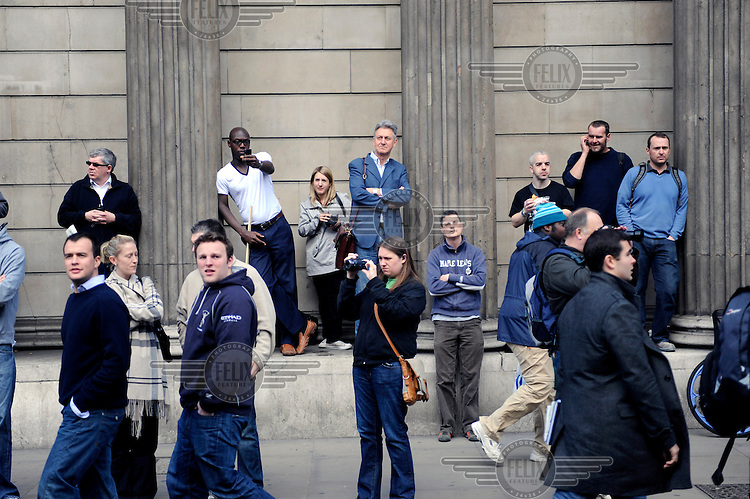 People watch the demonstration at the Bank of England as thousands of protestors descended on the City of London ahead of the G20 summit of world leaders to express anger at the economic crisis, which many blame on the excesses of capitalism.