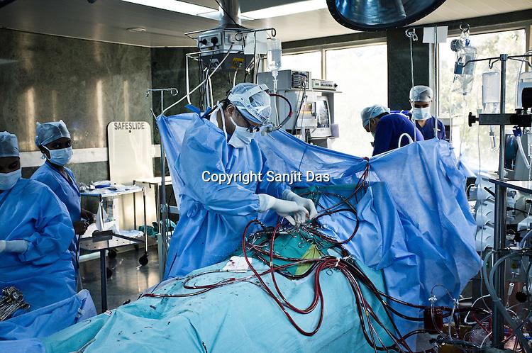 58 year old heart surgeon, Dr. Devi Prasad Shetty (centre) conducts an open heart surgery on Ajay Singh Goyal (23) at the Narayana Hrudayalaya in Bangalore, Karnataka, India. Photo: Sanjit Das/Panos
