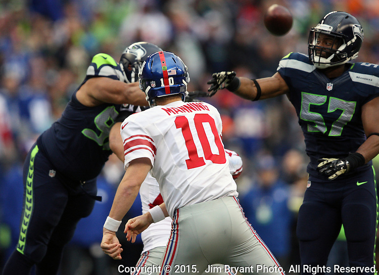 New York Giants quarterback Eli Manning (10) is pass rushed by defensive tackle Jordan Hill (97) and linebacker Mike Morgan (57) at CenturyLink Field in Seattle, Washington on November 9, 2014. The Seahawks  beat the Giants 38-17  ©2014. Jim Bryant Photo. All rights Reserved.