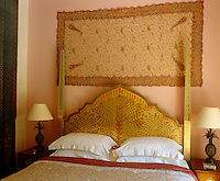 The ornate hand-painted headboard in this guest bedroom compliments the wall hanging