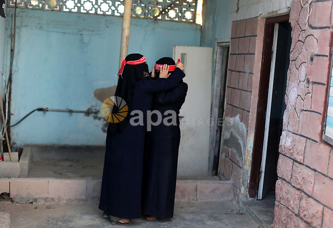 A Palestinian militant from the Democratic Front for the Liberation of Palestine (DFLP) adjusts the headband of her comrade as they get ready ahead of a training session in Rafah in the southern Gaza Strip June 10, 2013. Photo by Ashraf Amra
