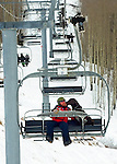 Crested Butte ski patrolman Shawn Williams and his chocolate avalanche rescue lab, Ziggy ride the chairlift.
