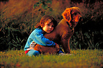 young child embracing pet dog
