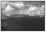 Scan of vintage black and white print. Negative file# 75-278. 1975. Parking lot topographic cloud study over car top.
