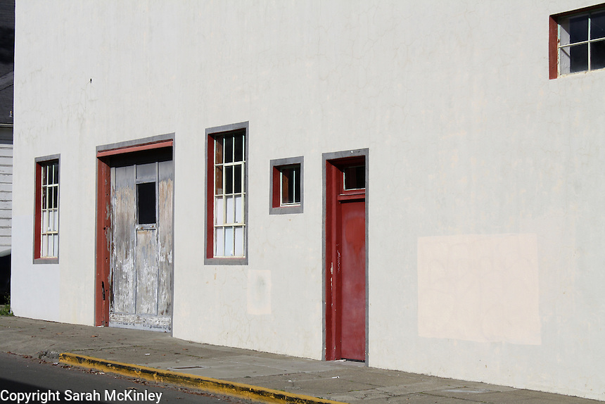 Several different doors and windows line the façade of a building in Ukiah in Mendocino County in Northern California.
