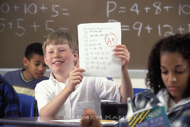 Student with A+ Math  Test in classroom