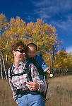 Mother hikes with infant daughter in backpack amidst fall color, Rocky Mtn Nat'l Park, CO