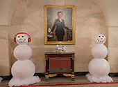 """The 2016 White House Christmas decorations are previewed for the press at the White House in Washington, DC on Tuesday, November 29, 2016. Snowmen are on either side of the portrait of former first lady Hillary Rodham Clinton in the Lower Cross Hall / Ground Floor Corridor. The first lady's office released the following statement to describe those decorations, """"This year's holiday theme, 'The Gift of the Holidays,' reflects on not only the joy of giving and receiving, but also the true gifts of life, such as service, friends and family, education, and good health, as we celebrate the holiday season.""""<br /> Credit: Ron Sachs / CNP"""