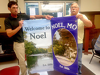 Sally Carroll/McDonald County Press<br /> Noel Street Superintendent Chris Craig (left) and Judge Robert Barth show off the two new banner designs that will soon adorn Noel's Main Street. Craig plans to put up about 10 new banners by week's end in an effort to beautify the city and prepare for all the summer visitors.
