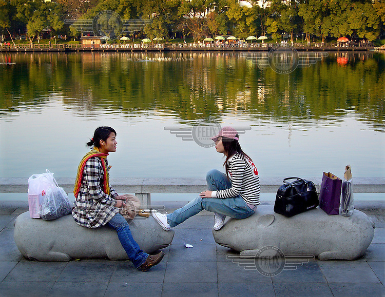 Two young women chat in the centre of Guilin after spending the afternoon shopping...