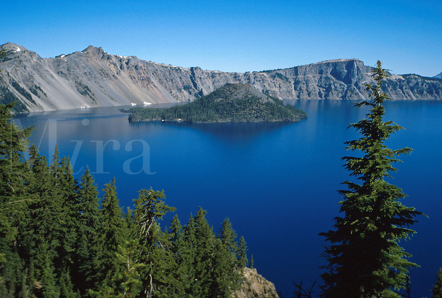 Crater Lake and Wizard Island. Blue water of Crater lake framed by granite rim and pine trees. mountain basin, scenic aerial landscape. Oregon, Crater Lake National Park.