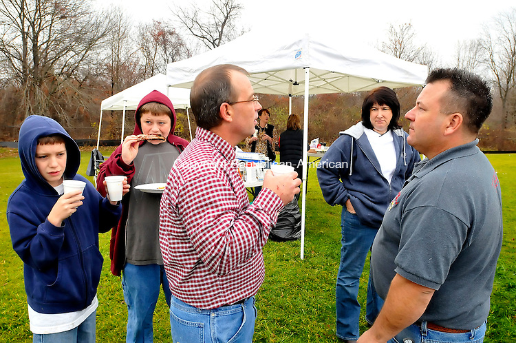 WATERTOWN, CT-26 NOVEMBER 2009-112609JS15- Glenn Middendorf of Watertown, and his wife Tammy Middendord, right, talks with Bob Karcher of Bethlehem, center as his two sons Johnny Karcher, 12, left and Bobby Karcher, 15, second from left, enjoy barbeque and drinks as they tailgate during the annual Torrington-Watertown Thanksgiving Day game Thursday at Watertown High School. Glen Middendorf if the owner of Hogtied Backyard BBQ and brought his smoker to the tailgate party. <br /> Jim Shannon Republican-American