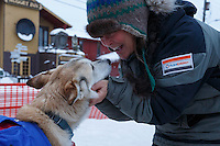 Linda Clarke, wife of musher Lachlan Clarke, gives one of their dogs attention at  the Nome finish chute shorlty after Lachlan finished on Sunday  March 22, 2015 during Iditarod 2015.  <br /> <br /> (C) Jeff Schultz/SchultzPhoto.com - ALL RIGHTS RESERVED<br />  DUPLICATION  PROHIBITED  WITHOUT  PERMISSION