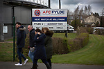 Supporters passing a sign advertising the day's fixture before AFC Fylde took on Aldershot Town in a National League game at Mill Farm, Wesham. The fixture was played against the backdrop of the total postponement of all Premier League and EFL football matches due to the the coronavirus outbreak. The home team won the match 1-0 with first-half goal by Danny Philliskirk watched by a crowd of 1668.
