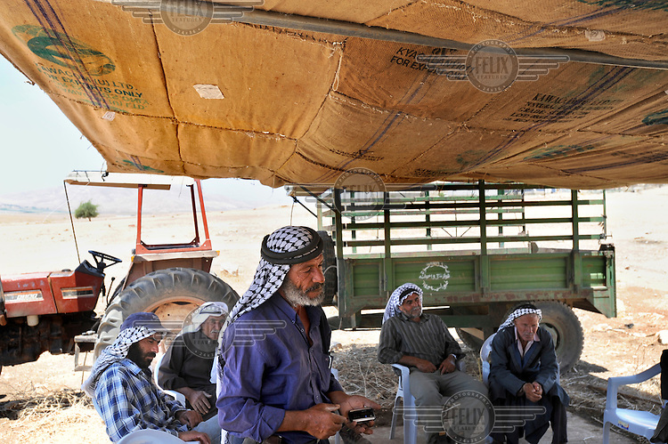 A group of Bedouin men gather in a hosting tent to discuss problems they face living in an encampment in Hadidyeh in the Jordan Valley. The Bedouin living here have been issued with eviction orders by Israeli authorities.
