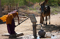 Indian woman pumping water from a well at Jawali village in Rajasthan, Northern India