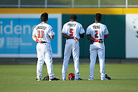 (L-R) Lansing Lugnuts outfielders Brock Lundquist (33), Reggie Pruitt (5), and Chavez Young (2) stand for the National Anthem prior to the game against the South Bend Cubs at Cooley Law School Stadium on June 15, 2018 in Lansing, Michigan. The Lugnuts defeated the Cubs 6-4.  (Brian Westerholt/Four Seam Images)