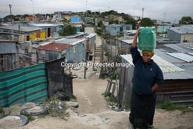 A woman carries a bucket of water in one of the poorest areas in Khayelitsha about 20 miles outside Cape Town. Photo by: Per-Anders Pettersson/Getty Images for Smithsonian Magazine.
