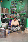 A man reads his newspaper while waiting for customers at his flour-grinding shop.