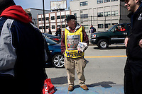 A vendor sells copies of the Boston Herald on the street outside the 2011 Boston Red Sox season opener at Fenway Park in Boston, Massachusetts, USA.