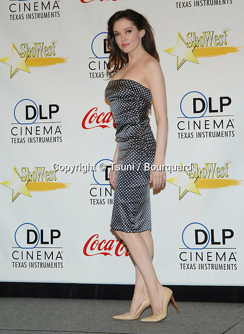 Rose McGowan backstage at SHOWEST in Paris hotel inLas Vegas.<br /> <br /> full lenght<br /> smile<br /> gray dress