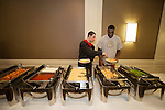 Aaron Craft puts some food on Evan Ravenel's plate during dinner