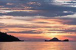 Triton Bay, West Papua, Indonesia; anchored near Macro Rock dive site, colorful sunset skies silhouette rocky islands in the distance and reflect off the water's rippled surface