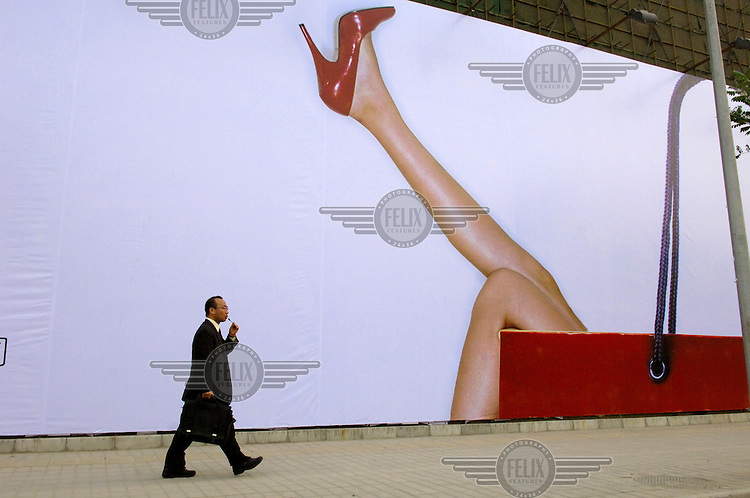 A businessman talking on his mobile phone while walking past a hoarding hiding the construction site of a luxury residential and commercial real estate development. The image used to advertise this site is typical of an increasing number of images objectifying women in modern China.