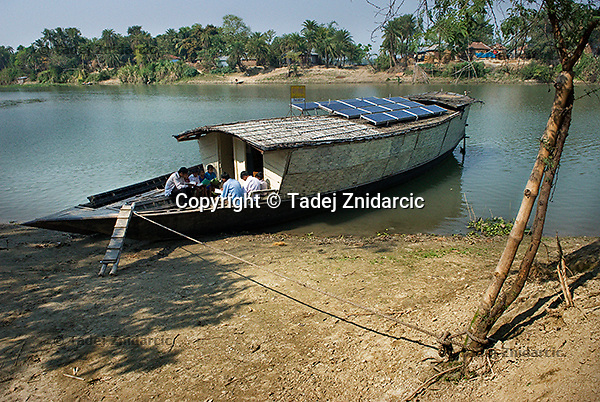 A library boat is docked on the Atrai river. One library boat visits three villages along the river in one day. Its solar panels provide energy for the onboard computers and for charging of the batteries that villagers use to power the solar lamps. (Photo by Tadej Znidarcic)
