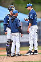 Asheville Tourists catcher Willie MacIver (23), pitching coach Mark Brewer and starting pitcher Riley Pint (27) during game one of a double header against the West Virginia Power at McCormick Field on April 20, 2019 in Asheville, North Carolina. The Tourists defeated the Power 12-7. (Tony Farlow/Four Seam Images)