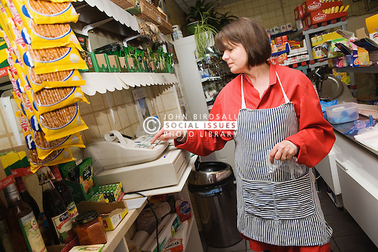 Shop owner using the till to add up customers bill in Polish Delicatessen,