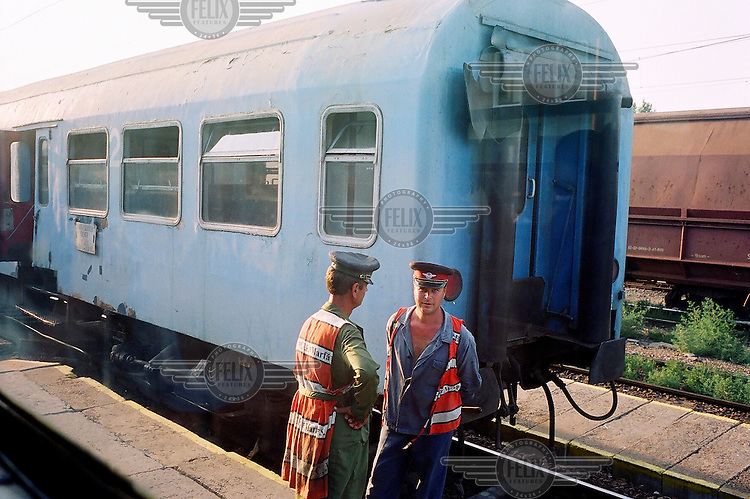 National rail workers talking on the platform beside a train travelling to Bucharest. /Felix Features