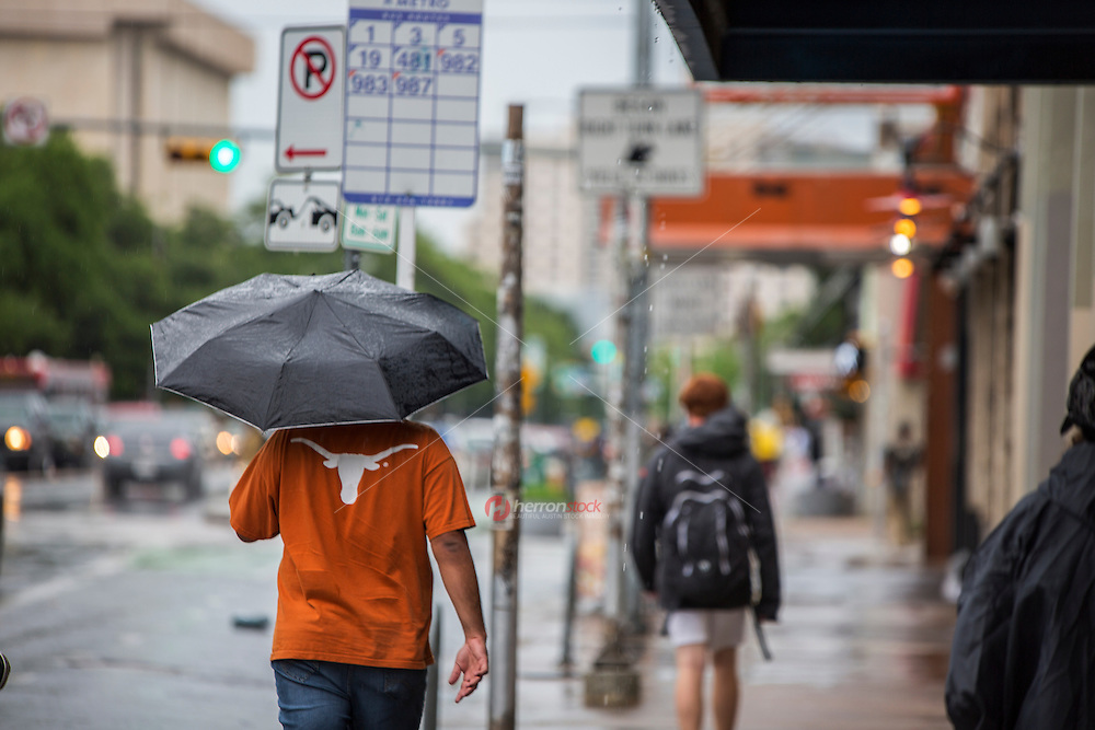Close up of students walking in a rain storm on UT Drag next to the University of Texas campus in downtown Austin, Texas - Stock Image.