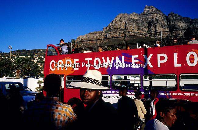 CAMPS BAY, SOUTH AFRICA - JANUARY 1: A bus with tourists drives along the beach road as the sun sets on January 1, 2003 in Camps Bay outside Cape Town, South Africa. Camps Bay has some of the best beaches and most expensive properties in the country, and it?s a popular place for locals and foreign visitors. .(Photo: Per-Anders Pettersson/Getty Images)........