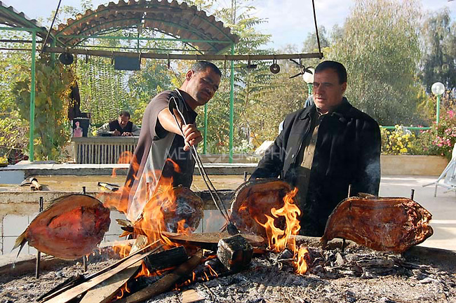 IRAQ, MOSUL:  Two men cook masgoof (a traditional fish recipe) near the Dijla river...Photo by Hakar Said/Metrography