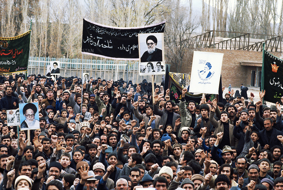 TEHRAN, IRAN - JANUARY 1980: A group of protesters holding banners and photos of Ayatollah Mohammad Kazem Shariatmadari, during a demonstration to show their support towards him. Ayatollah Mohammad Kazem Shariatmadari was among the most senior leading twelve Shi'a clerics in Iran and Iraq. (Photo by Reza/Getty Images)<br />