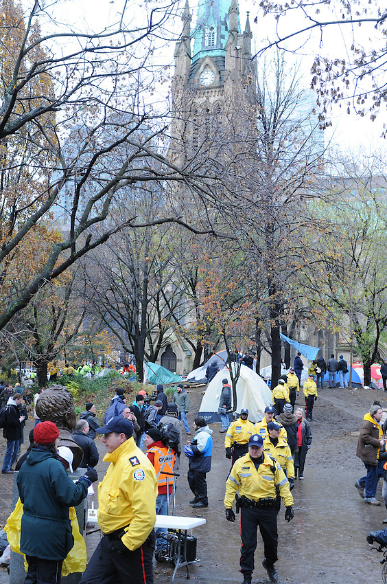 November 23, 2011, Toronto Police in significant numbers deployed during the predawn hours this morning, beginning the process of evicting the Occupy Toronto tent camp from St. James Park.  Here Police and city workers comb the protest tent site amidst protest supporters and media people.