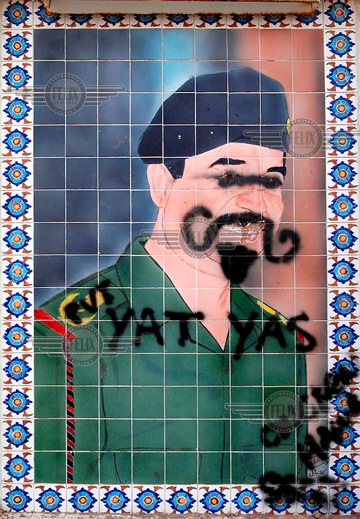 Defaced portrait of ex-President Saddam Hussein.