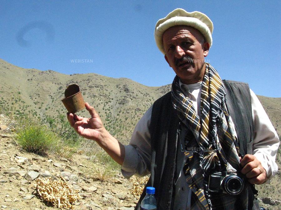 """AFGHANISTAN - VALLEE DU PANJSHIR - 17 aout 2009 : Reza, lors d'une marche dans les montagnes encadrant la vallee du Panjshir. Reza tient dans la main un boite de conserve rouillee, vestige d'un ancien campement de l'armee russe pendant la guerre d'Afghanistan de 1979 - 1989. .La photographie appartient a la serie """"Il etait une fois l'Empire russe"""". ..AFGHANISTAN - PANJSHIR VALLEY - August 17th, 2009 : Reza on a walk through the moutains of the Panjshir Valley. In his hand is a rusted tin can, a remnant from a Russian army camp from the Afghan war of 1979-1989..The photograph is part of the series """"Once Upon a Time, the Russian Empire."""""""