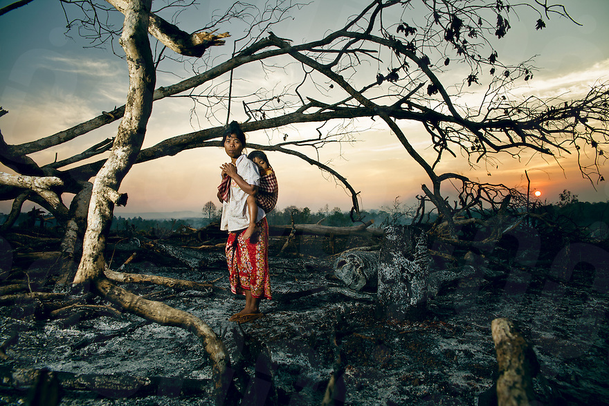February 24, 2011 - Mondulkiri (Cambodia). A  Pnong mother poses poses with her baby in front of burned trees in Pou Pring village. Indigenous people who live in this part of the country are among the most affected by logging, and the consequent loss of natural resources of which they are dependant upon. © Thomas Cristofoletti / Ruom
