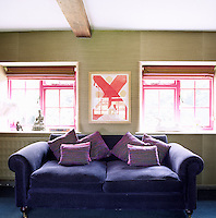 In the living room the decoration is an eye-catching combination of a violet-upholstered sofa positioned between two windows with shocking pink woodwork